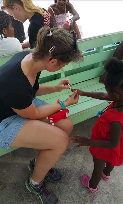 A member of Carlson's group paints a little girl's nails.
