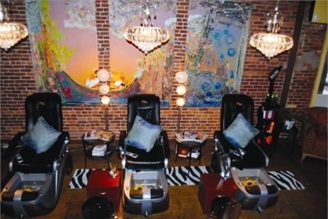 The stylish pedicure parlor features three large Shiatsu massage chairs, complete with color therapy bowls and shimmering cerulean pillows.