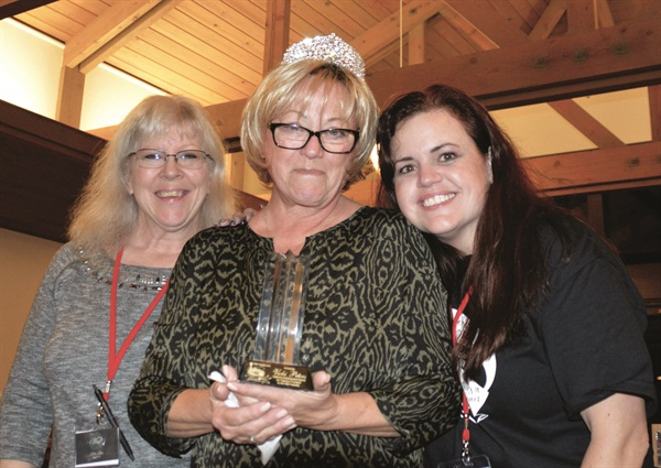 <p>Flanked by Ellen Torchia (left) and Jessica Hoel, Vicki Peters accepts a lifetime achievement award and crown. Many of the participants spoke about the impact she's had on their lives. </p>