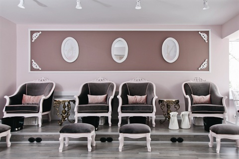 Located directly behind the manicure stations is the pedicure area, which seats four clients on an elevated platform in pale pink wooden chairs.