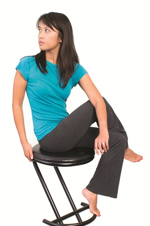 <p>Sit up straight on a chair with no arms. Cross the right leg over the left and drape the left arm over the right leg so the elbow is on the outside of the right knee. Without rounding your shoulders, twist to the side to stretch your spine and lower back muscles. Hold for a count of 10.</p>
