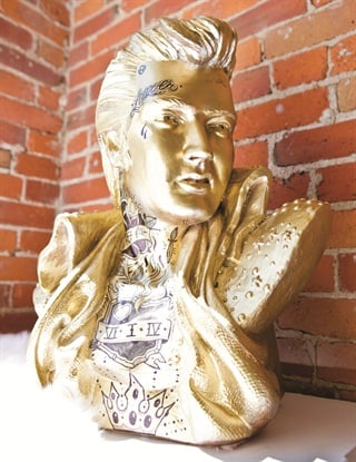 "<p>The ""mascot"" of the salon is a tattooed, golden Elvis statue, which reflects Suárez-Brentzel's love for The King.</p>"