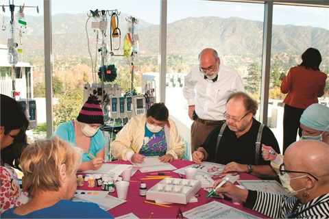 <p>George Schaeffer (seated, third from right) joins City of Hope patients in creating artwork to support the dinner in his honor.</p>