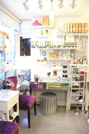 """<p class=""""NoParagraphStyle"""">Lining the storefront window is The Studio's waiting area, which is decorated with mirrored furniture, eye-catching nail polish displays, and royal purple chairs.</p>"""