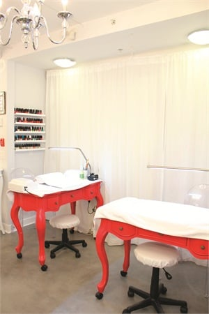 """<p class=""""NoParagraphStyle"""">The Studio's manicure area features bright red tables that give the corner a modern color pop. During services, clients sit in ghost chairs, or transparent seats, made from plexiglass.</p>"""
