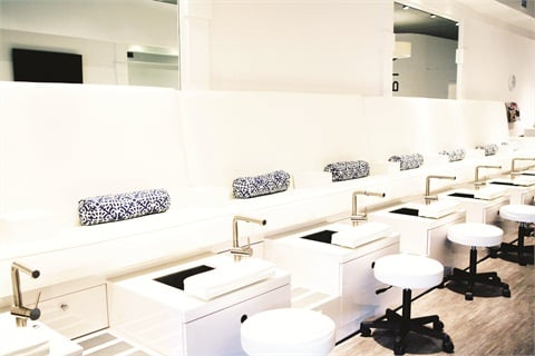 <p>Custom-designed pedicure benches feature jet-free stainless-steel basins for sanitation purposes. To compensate, nail techs focus on the massage element of the treatment.</p>