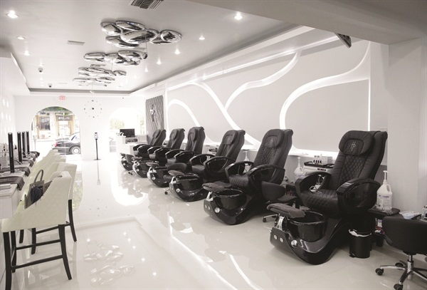 <p>High-end black and white chairs furnish the salon, while chrome nail polish droplets hang from the ceiling.</p>