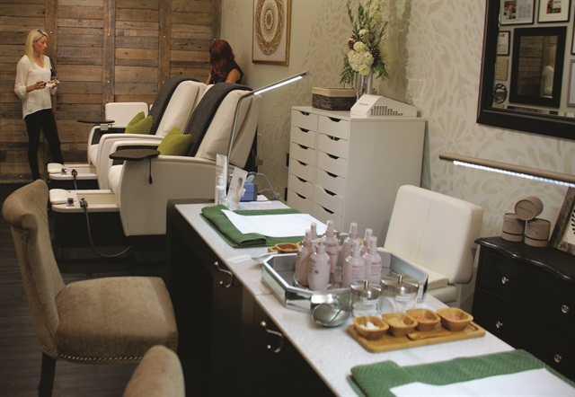 The tan tones of the wallpaper and furnishings promote a calm atmosphere for clients.