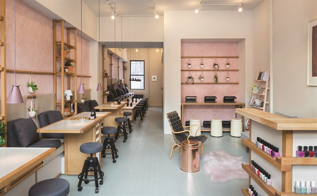 <p>The salon interior hosts an abundance of plants and fresh flowers along the sides of each station, and a rack of thought-provoking books.</p>