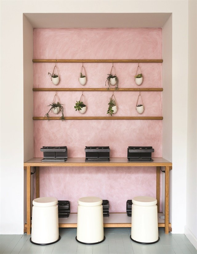 "The ""millennial"" pink walls add softness to the custom-made wooden shelves throughout the space."