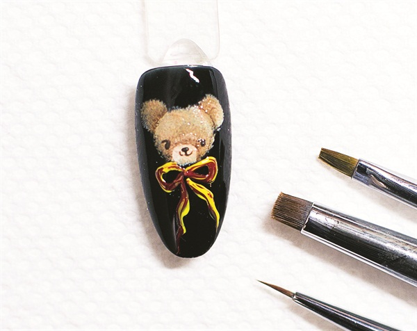 <p>6. Use AnGel Artist Brush No. 7 and draw out the ribbon in yellow. Cure for 10 seconds, and then fill in the ribbon with red. Cure for another 10 seconds. When finished, cover the artwork with the top coat of your choice and do a full cure for the manufacturer's recommended time.</p>