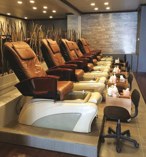 A row of bamboo divides the rows of pedicure chairs in the salon.
