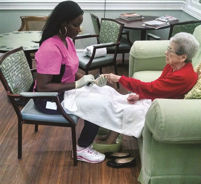 <p>Nail tech Tricia Turner owns Senior Feet, A Place for Seniors, in Virginia Beach, Va. She's seen here tending to a client in a nursing home.</p>