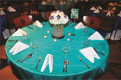 <p>Turquoise tablecloths with blue-accented centerpieces for the reception. <em>Photo courtesy of Venu & Bala Varanasi.</em></p>
