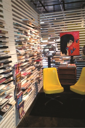 <p>This bookshelf creates a semi-private space for a drying area, plus offers salon guests a view into the cafe.</p>
