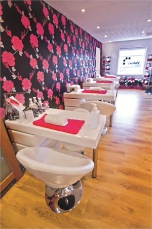 """With flamboyant wallpaper and hot pink accents, Polish Nail & Beauty features decor described as """"girly, pink, and glitzy,"""" according to Samantha """"Sammy"""" Grant, the salon's founder and co-owner."""