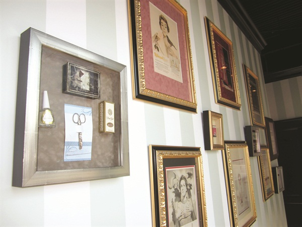 <p>Vintage nail product ads as well as framed product bottles and implements line the hallway wall between the rooms.</p>