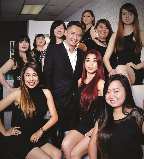 <p>Tracy Tran and Tomson Nguyen are seated with the GLO Nail Bar staff.</p>