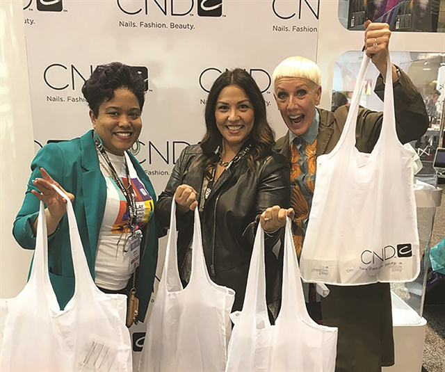 "Left to right: CND education ambassador Zsanea Hatcher, Diane Diaz, and Jan Arnold show off Diaz' loot. ""Zsanea was my personal shopper at the booth. Thank goodness for her help as I was like a kid in a candy store with no direction,"" says Diaz."