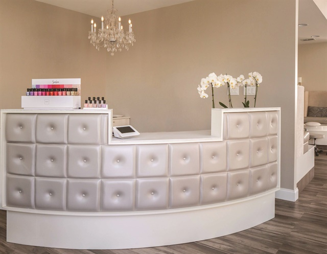 <p>The curved, tufted reception desk and a chandelier add a graceful femininity.</p>