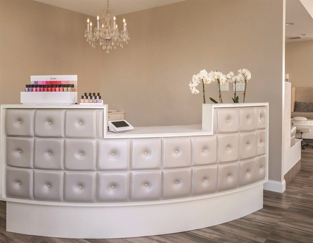 The curved, tufted reception desk and a chandelier add a graceful femininity.