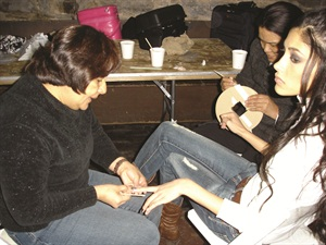 <p>One of Honey's assistants works on a model, while another helps out with the glue dots used to apply the tips.</p>