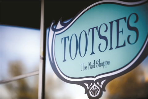 "<p class=""NoParagraphStyle"">This large ""Tootsies the Nail Shoppe"" sign sits outside Tootsies' Washington Park location. Its color and design echo the decor of the salon's interior, which is described by salon owner Castle Searcy as ""New York art deco.""</p>"