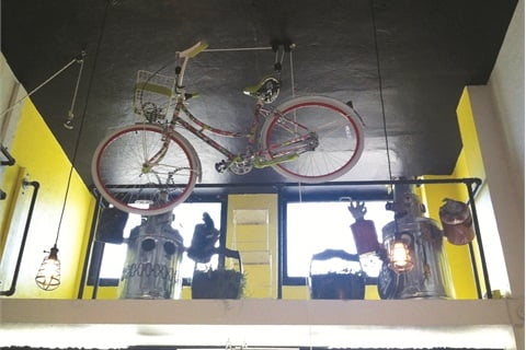 A bike hangs at the front of the salon's loft. A ladder was installed to reach the loft so the Art Deco windows could be opened and closed.