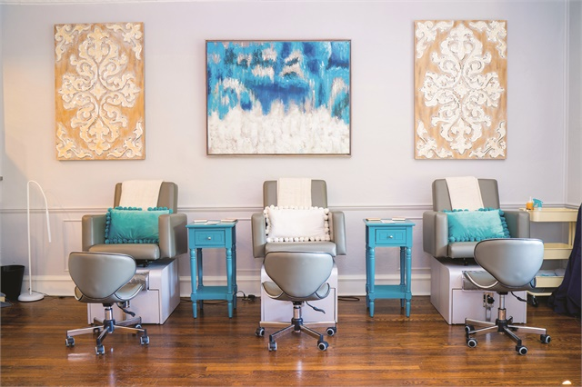 The salon has a clean look with original wood floors, and gray and white furniture and walls.