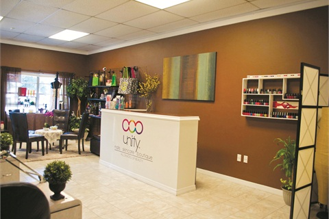 "<p class=""NoParagraphStyle"">Upon entering Unity, customers immediately see the front desk, which display's the salon's logo. Unity's boutique section and waiting area are also visible in the background. The main colors are earthy and neutral.</p>"