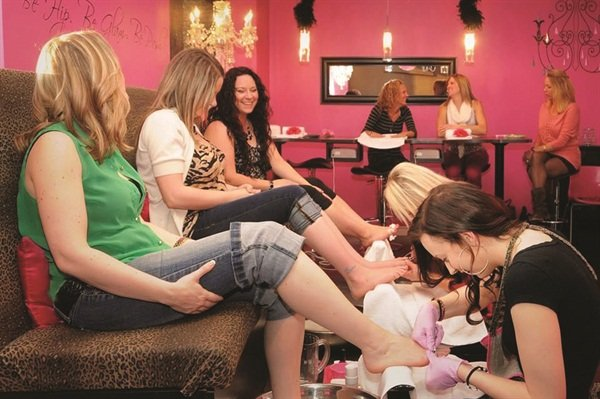 <p>Clients receive pedicures at Posh Pedicure Lounge. Leopard and pink accents are the salon's signature decor.</p>