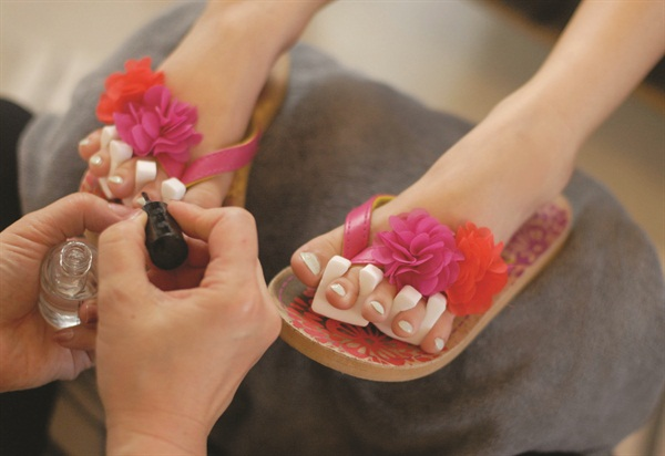 A Polish nail tech paints the toes of a customer attending a 9-year-old's birthday party hosted at the salon.