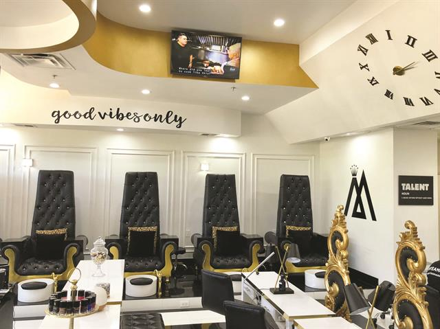 The custom-made pedicure chairs fit the salon's black and gold theme.