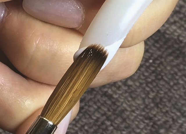 Nail tech Geneva Holcomb uses a practice tip between clients when she's switching from one enhancement medium to another.