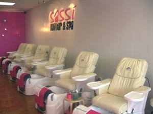 <p>Pedicure thrones line one wall with a manicure bar along the opposite wall. The salon features trendy design elements like pink accent walls, interesting lighting, and flowing curtains. </p>