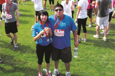 Victor Munoz from the shipping department and his daughter, Cynthia G. Munoz, celebrate the completion of the 5K inside the L.A. Memorial Coliseum.