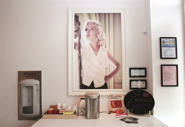 <p>A self-serve beverage station is available for clients, and stunning images of Marilyn line the salon walls.</p>