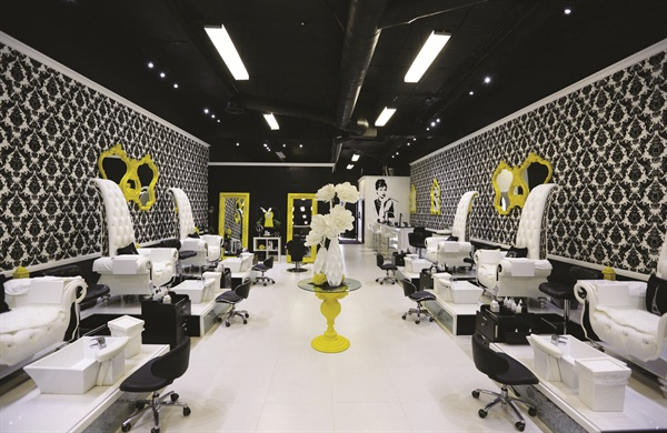 At Laqué's North Hollywood location, bright yellow framed mirrors are offset by white custom-made pedicure and manicure stations, allowing the nail and beauty bar to pop.