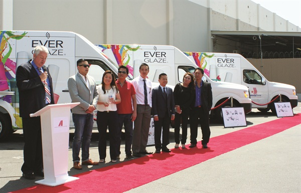 <p>Charlie Loveless, AII V.P. of operations, presents customized vans to the owners of Beauty Zone, Kashi Beauty, and Nails West.</p>