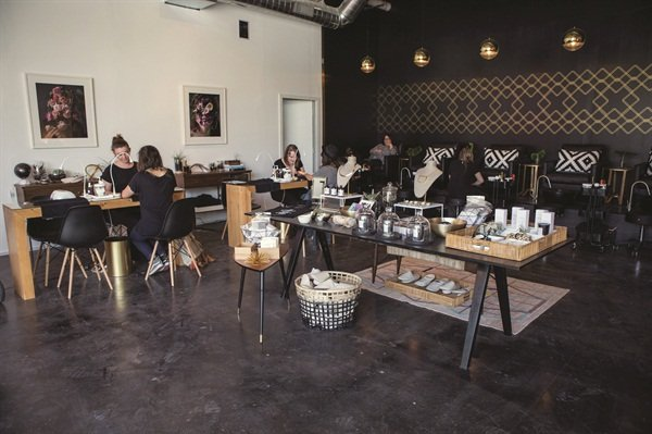 <p>Base Coat often hosts parties and events in this welcoming space. The center table is for retail, featuring eco-friendly local and national goods. The wall above the manicure station holds two photos by artist Kristen Hatgi Sink.</p>