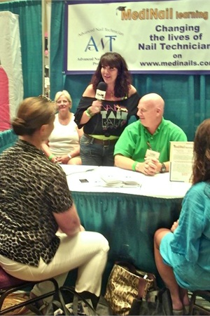 """<p><span id=""""fbPhotoSnowliftCaption"""" class=""""fbPhotosPhotoCaption""""><span class=""""hasCaption"""">Athena Elliott with Nail Talk Radio conducted booth to booth interviews with educators, owners, and nail techs. This interview took place at the <span id=""""fbPhotoSnowliftCaption"""" class=""""fbPhotosPhotoCaption""""><span class=""""hasCaption""""><span id=""""fbPhotoSnowliftCaption"""" class=""""fbPhotosPhotoCaption""""><span class=""""hasCaption""""><span id=""""fbPhotoSnowliftCaption"""" class=""""fbPhotosPhotoCaption""""><span class=""""hasCaption"""">MediNail Learning Center booth.</span></span></span></span></span></span><br /></span></span></p>"""