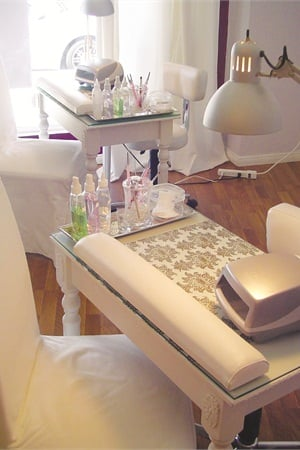<p>Each manicure station features a collection of treatment products, a UV light for curing, and an ergonomic wrist pad. Although the stations have an overhead light, an abundance of natural light streams in from the salon's floor-length windows.</p>