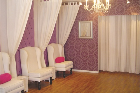 <p>Beneath Stay Polished Nail Boutique's iconic baroque-style chandelier lies the salon's pedicure station made up of three pedicure chairs, each separated by a simple white curtain.</p>