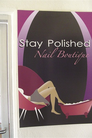 <p>Stay Polished Nail Boutique's stylized logo is displayed on the salon's exterior wall adjacent to the front door.</p>