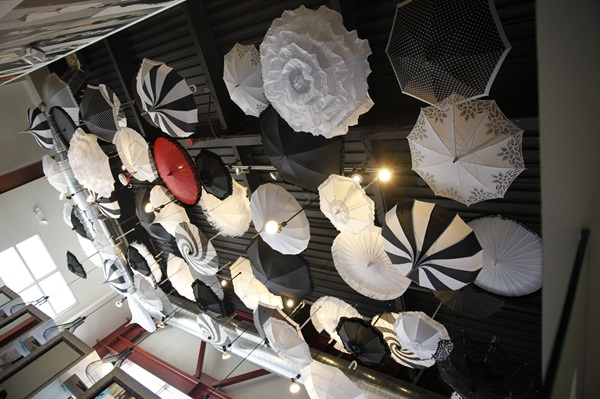 The ceiling of the blow dry bar is lined with umbrellas.