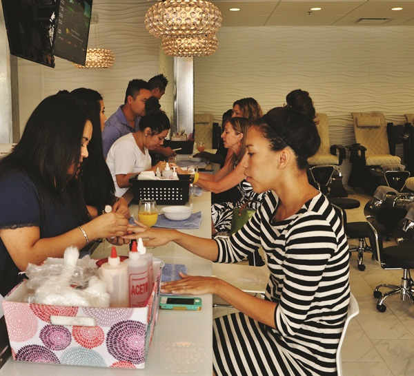 <p>A client looks on as a Polished nail tech works on her manicure.</p>