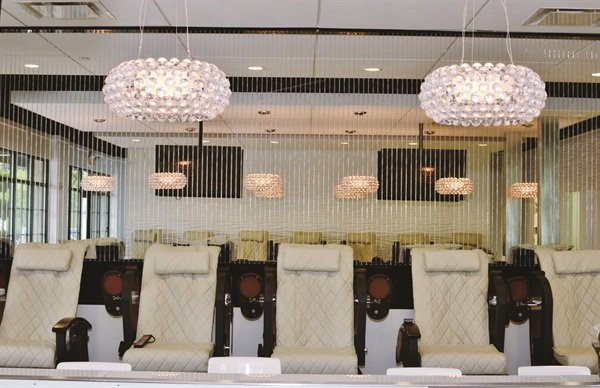 The tan and brown hues of the pedicure thrones accentuate the hanging lights and white walls of the nail bar.