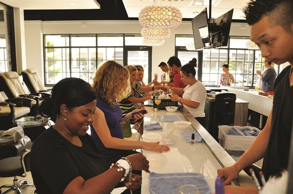 <p>Nail techs line up behind the nail bar and prepare to serve incoming clients.</p>