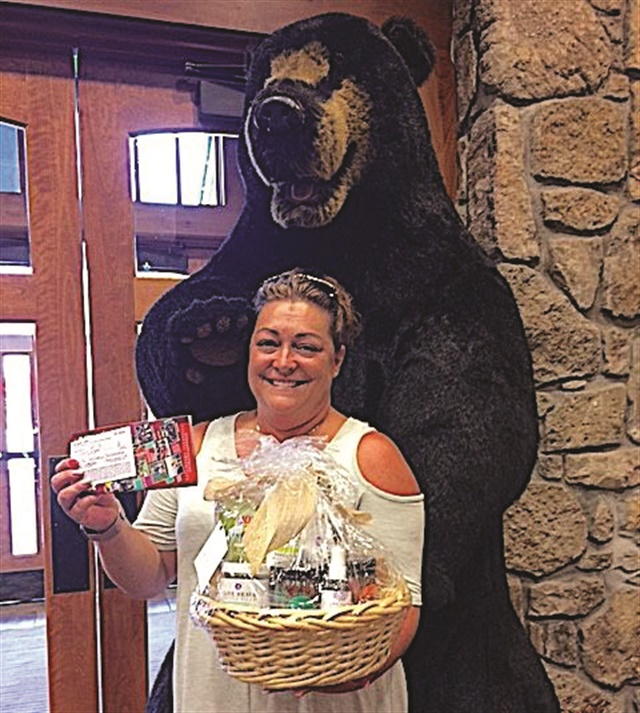 Thistle Farms raffle winner Dana Shew holds a spa products gift basket and her $1,200 pass to all the Gatlinburg attractions.