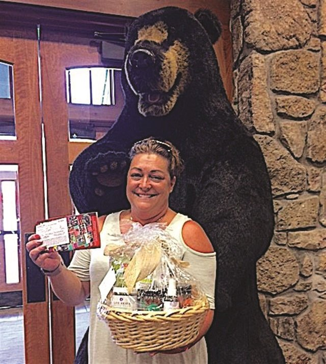 <p>Thistle Farms raffle winner Dana Shew holds a spa products gift basket and her $1,200 pass to all the Gatlinburg attractions.</p>
